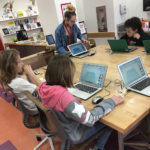 children with laptops seated around a table