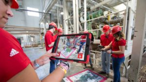 Four people hold ipads and interact with an AR pad in a feed mill
