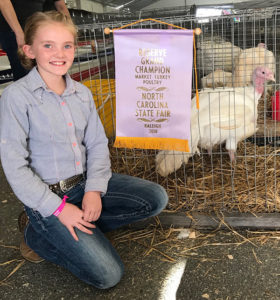 Caroline Scarlett kneeling beside her caged turkey