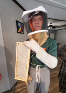 a young many holding part of a bee hive insert and wearing beekeeping protective clothes